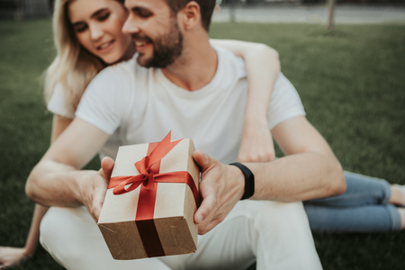 Focus on small present box in male hands. Hilarious twosome sitting on grass and embracing