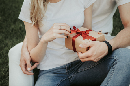 Woman is embraced by her boyfriend and holding box with gift. They locating on grass