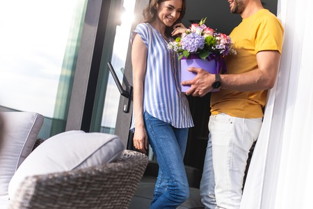 Happy male is holding beautiful and expensive bouquet of flowers for his cute girlfriend while standing at the entrance to terrace