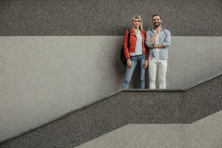 L'uomo bello gioioso è in piedi accanto alla bella signora davanti al muro grigio. Stanno guardando la fotocamera con un sorriso. Copia spazio sul lato sinistro