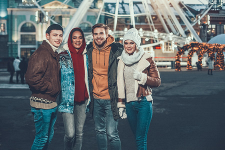 Portrait of cheerful females and smiling men hugging while walking on street during cold evening Imagens
