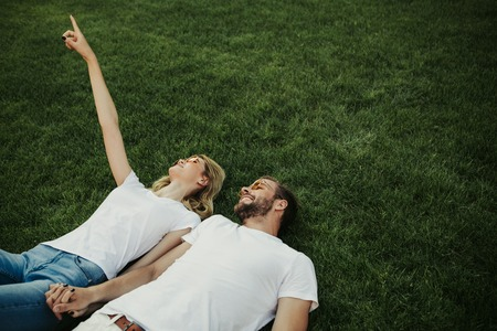 Top view of cute happy twosome lying on lawn and holding hands. Woman pointing up. Copy space on right side