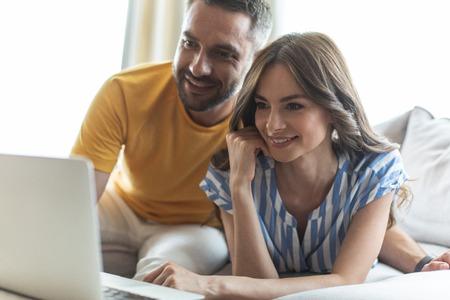 Beautiful woman and smiling man watching photos on laptop