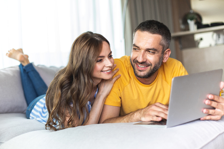 Beautiful couple is lying on sofa and looking on laptop while smiling