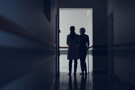 Lady with cane is leaning on medical worker hand. They are walking together through corridor. Copy space in left side Banco de Imagens