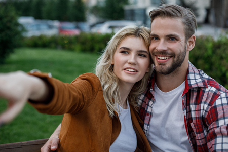 Cheerful young woman embraced by her boyfriend pointing aside. They looking there with bright smile