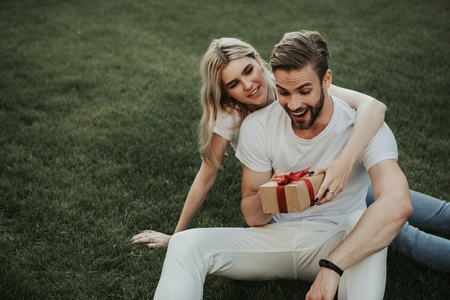 Hilarious woman is giving present to her exited boyfriend. They locating on green lawn. Copy space on left side Imagens