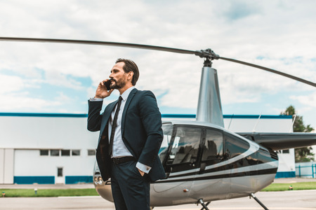 Confident experienced businessman in elegant suit standing on the helicopter platform and having an important phone talk