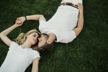 Top view of relaxed young couple lying on green lawn with closed eyes. They holding hands