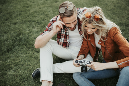 Cheerful young twosome sitting on green grass and watching photos on camera. Copy space on left side Stock Photo