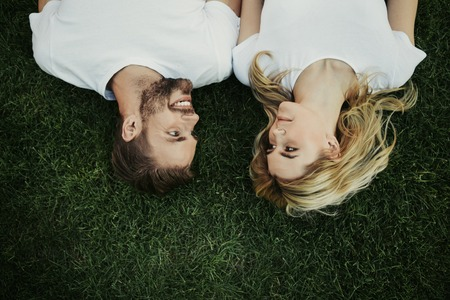 Top view of happy smiling couple is lying on green lawn and glancing at each other with tenderness Banco de Imagens