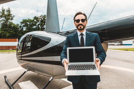 Attractive elegant businessman standing with the helicopter behind his back and smiling while showing the screen of his laptop