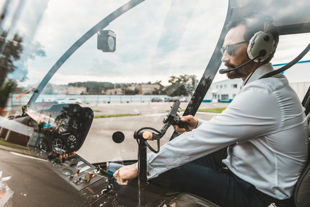 Serious professional pilot sitting in the helicopter cabin and pushing the buttons on the dashboard