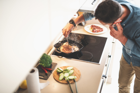 Top view of young gentleman cooking meat on frying pan while having phone conversation