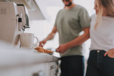 Blurred portrait of man cooking breakfast for his woman. Focus on coffee mug with coffee maker Stock fotó