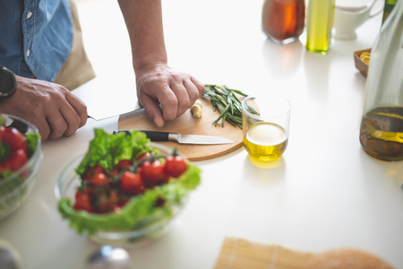Close up of male hands with knife preparing ingredient for fresh salad. Glass of olive oil and bowl with vegetables on kitchen table