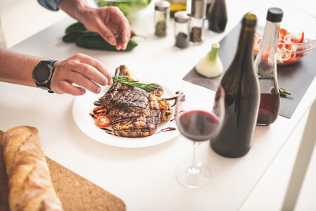 Close up of male hands putting herb on grilled meat. Gentleman standing near white kitchen table with wine, vegetables and spices