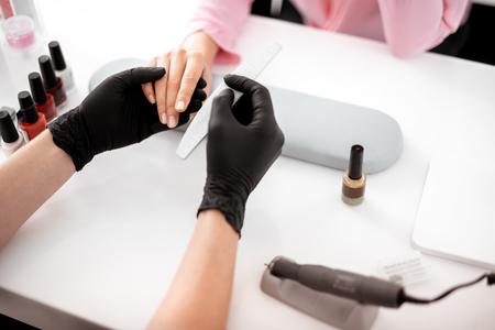 Manicurista experimentado con guantes negros y sosteniendo la mano de su cliente mientras pule las uñas largas Foto de archivo
