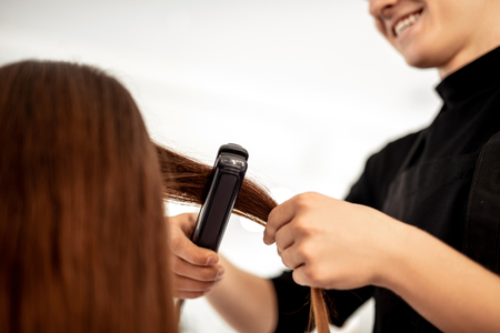 Positive enthusiastic hairdresser feeling satisfied with his work and smiling while using flattening iron on long hair