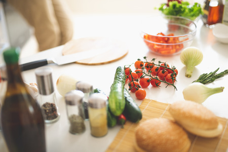 Fresh tomatoes, cucumber, onion, rosemary and bowl of chopped red pepper on desk