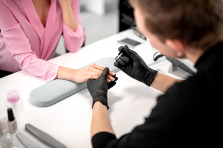 Professional manicurist in black gloves holding nail color and touching the hand of his client while working