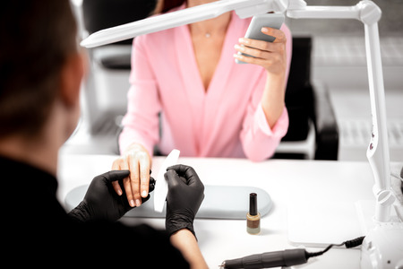Relaxed young lady sitting with modern smartphone while professional manicurist polishing her nails Archivio Fotografico