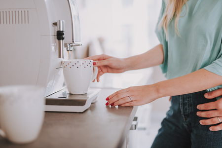 Close up photo of woman making coffee on the kitchen