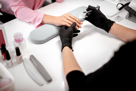 Professional manicurist sitting in front of the client and holding her hand while using nail brush during the procedure