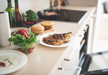 Kitchen table with roasted meat, vegetables, burger buns and paper towel Stock Photo