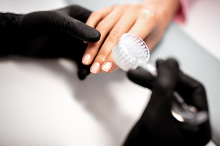 Close up of the professional manicurist in rubber gloves cleaning the nails of his client while using special nail brush Stock Photo