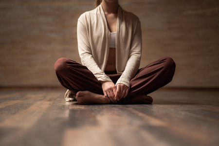 Young lady in comfortable clothes sitting on the floor in lotus pose while meditating alone Stock Photo
