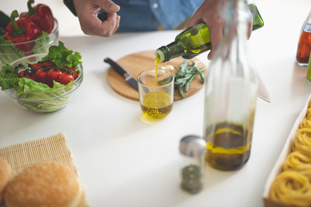 Close up of male hands pouring olive oil in glass. Bowls with fresh vegetables, cutting board with garlic and knife on table