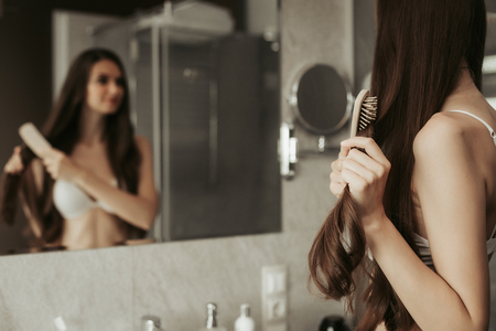 Portrait of positive combing hair while keeping hairbrush. She reflecting in mirror in bathroom