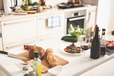 White kitchen desk with delicious seasoned meat, glass of alcohol drink and bakery. Stove and oven on blurred background
