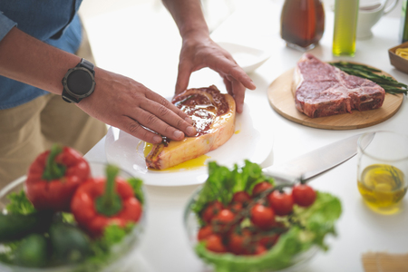 Close up of male hands greasing raw beef steak with olive oil. Fresh vegetables, knife and cutting board on blurred background Stock Photo