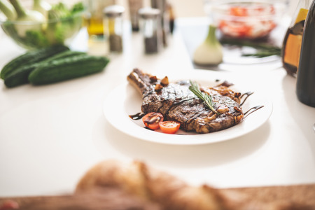White kitchen table with delicious seasoned beef steak on plate Stock Photo