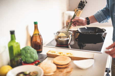 Close up of male hand holding kitchen spoon with tagliatelle. He is standing near stove Stock Photo