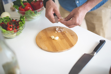 Close up of male hands holding knife while peeling garlic. Bowls with tomatoes, lettuce, cucumber and red bell pepper on kitchen table