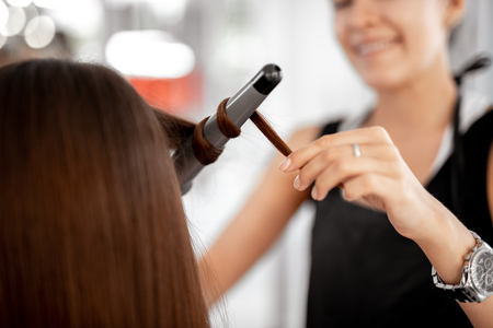 Professional experienced hairdresser smiling and touching the hair of her client while using curling iron at work Stock Photo