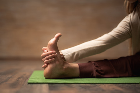 Close up of the foot of young lady being on the green yoga mat and touching the foot with one hand