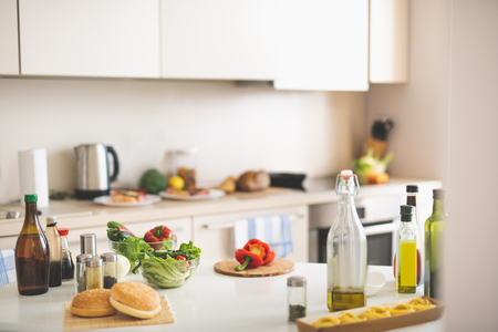 Kitchen desk with cutting board, red bell pepper, olive oil, lettuce, spices and burger buns