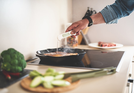 Close up of male hand checking readiness of meat on frying pan