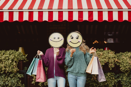 Portrait of two ladies hiding under carton icons of smiling face. They holding colorful shopping bags while standing near outdoor cafe Stock Photo