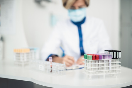 Professional facility investigations in healthcare system. Close up portrait of medicine board with test tubes while laboratory worker making notes in lab office