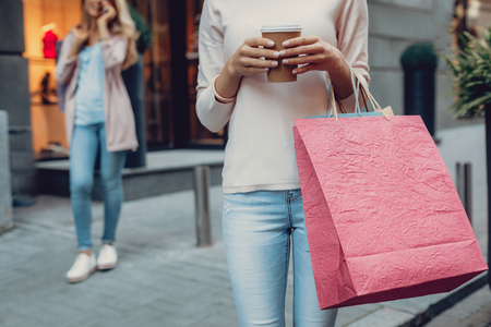 Cropped portrait of young lady with shopping bags holding cup of coffee. Elegant woman having phone conversation on blurred background