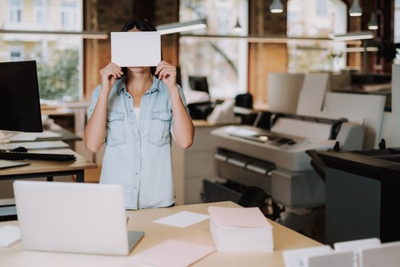 Waist up portrait of girl in blue shirt hiding under white sheet of paper. She is standing near office table with laptop