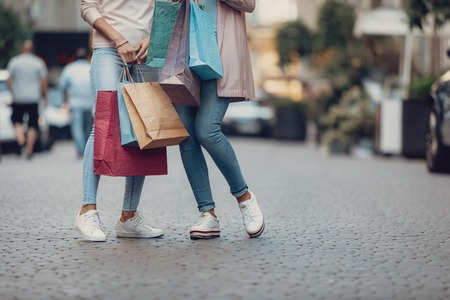 Cropped portrait of young woman and her mother holding colorful shopping bags