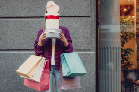 Portrait of stylish girl holding shopping bags and hiding under presents while standing on the street