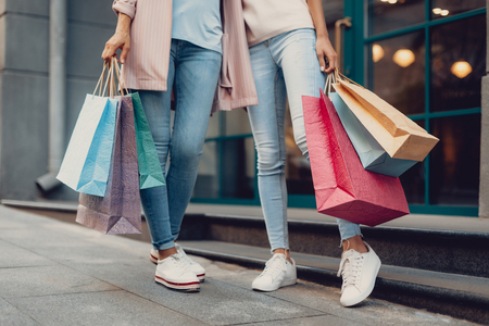 Look what we got. Cropped portrait of young lady and her mother holding colorful shopping bags Stock Photo