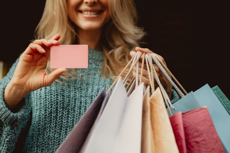 I can buy anything i want. Cropped portrait of smiling middle-aged lady holding pink card and shopping bags Stock Photo